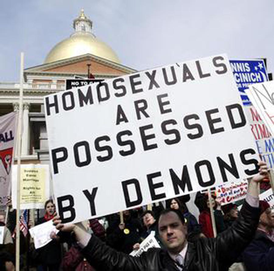 """Gay marriage opponent Leonard Gendron, a local pastor, holds a sign reading """"Homosexuals are Possessed by Demons"""" outside the Massachusetts State House in Boston March 11, 2004 where the Massachusetts Legislature is debating an amendment to the state's constitution banning gay marriage.  On November 11, 2003 the Massachusetts Supreme Judicial Court ruled that the state must issue marriage licenses to gay couples.       REUTERS/Brian Snyder"""